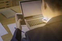 Bemannen Sie Hand unter Verwendung des Handys mit Laptop auf hölzerner Tabelle mit Blatt stockfoto