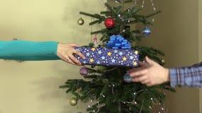 Bemannen Sie Handanwesendes Geschenk für Frau auf Weihnachtsbaumhintergrund stock video