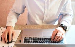 Bemannen Sie Handarbeit mit Laptop auf grauer Tabelle stockfoto