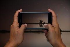 Bemannen Sie Handholding und mit Mobile, Handy, intelligente Telefonphotographie und See in der Nacht mit den Sternen im Himmel Stockfotografie