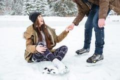 Bemannen Sie helfendes Mädchen, um auf der Eisbahn zu stehen stockfotografie