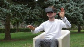 Bemannen Sie herum schauen in einer Welt der virtuellen Realität unter Verwendung VR-Gläser und -blätter, die auf ihn fallen stock footage