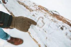 Bemannen Sie Herzsymbol des abgehobenen Betrages auf Schnee im Wald Stockfotografie