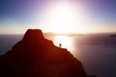 Bemannen Sie Hügel oben klettern, um die Spitze des Berges über Ozean zu erreichen Stockbilder