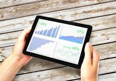 Bemannen Sie Hände mit digitaler Tablette mit Geschäftsdiagramm auf einem Schirm an Stockfoto