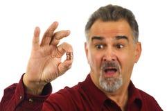 Bemannen Sie Holdingmünzen mit Blick des Schlages auf seinem Gesicht Lizenzfreie Stockfotos
