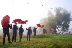 Bemannen Sie Holdingregenschirm und das Gehen durch die fores Lizenzfreie Stockfotografie