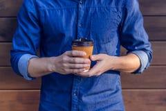 Bemannen Sie im Jeanshemd, das Schale frischen Kaffee gegen den braunen Hintergrund hält, der nah herauf Foto von gesundem grobem lizenzfreie stockfotos