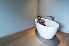 Bemannen Sie innerhalb einer Luxusbadewanne in der modernen Wohnung Stockfotografie