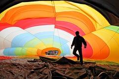 Bemannen Sie innerhalb eines bunten Heißluftballonaufblasens Lizenzfreie Stockbilder