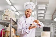 Bemannen Sie Konditor mit einem Kuchen in seinen Händen im Gebäck Lizenzfreies Stockfoto
