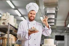 Bemannen Sie Konditor mit einem Kuchen in seinen Händen im Gebäck Stockbilder