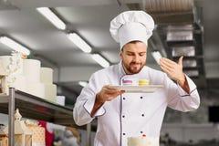 Bemannen Sie Konditor mit einem Kuchen in seinen Händen im Gebäck Stockfotos