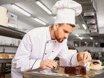 Bemannen Sie Konditor mit einem Kuchen in seinen Händen im Gebäck Lizenzfreies Stockbild