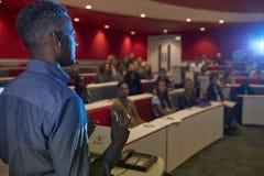 Bemannen Sie konferierende Studenten in einem Hochschulvortragtheater stockfotos