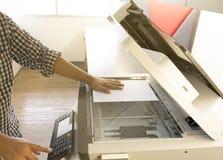 Bemannen Sie Kopierpapier vom Fotokopierersonnenlicht vom Fenster Lizenzfreie Stockfotografie