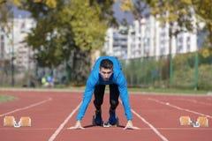 Bemannen Sie Läufer im blauen Hemd und in den kurzen Hosen und Sportschuhe in der stabilen Position vor Lauf am Anfang des Rennen stockfotografie