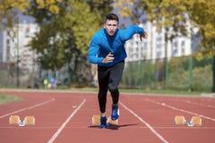 Bemannen Sie Läufer im blauen Hemd und in den kurzen Hosen und Sportschuhe in der stabilen Position vor Lauf am Anfang des Rennen stockfoto