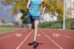 Bemannen Sie Läufer im blauen Hemd und in den kurzen Hosen und Sportschuhe in der stabilen Position vor Lauf am Anfang des Rennen lizenzfreie stockbilder