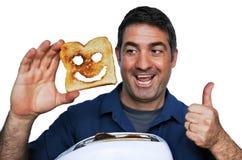 Bemannen Sie Lächeln und Griffe eine gute Scheibe des Toasts Stockfotos
