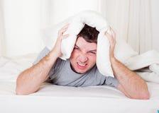 Bemannen Sie leidenden Kater und Kopfschmerzen mit Kissen an stockbilder