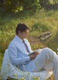 Bemannen Sie Lesebuch am Morgen durch einen Teich stockbilder