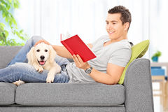 Bemannen Sie Lesebuch und mit einem Welpen zu Hause sich entspannen Lizenzfreie Stockfotografie