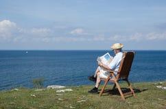 Bemannen Sie Lesezeitung in einem Stuhl an einer schönen Ansicht Stockbilder