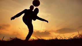 Bemannen Sie Münzen ein Ball Europäer das Fußballfußball-Freistilschattenbild am Sonnenlicht des Sonnenuntergangs draußen Mannsch stock footage