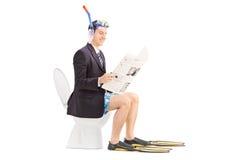 Bemannen Sie mit der Schnorchel, welche die Nachrichten auf einer Toilette liest lizenzfreie stockbilder