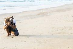 Bemannen Sie mit Hippie-Wandererrucksack allein sitzen und das Halten der Kamera Stockbilder