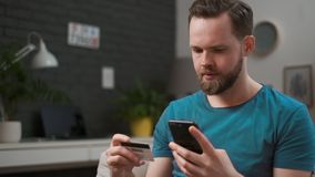 Bemannen Sie mit Kreditkarte am intelligenten Telefon zu Hause zahlen Kaukasischer Kerl, der vorbei Smartphone f?r das on-line-Ei stock video