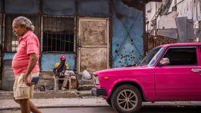 Bemannen Sie mit rosa Oldtimer im Havana, Kuba stockbilder
