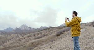 Bemannen Sie nehmen Schüsse auf Mobile, bei der Stellung auf Hintergrund von Bergen und von Felsen stock footage