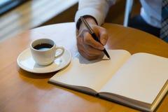 Bemannen Sie Notizbuch mit Stift und Kaffee auf altem Holztisch Lizenzfreie Stockfotografie