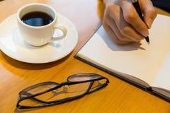 Bemannen Sie Notizbuch mit Stift- und Kaffeegläsern auf Holztisch Stockbilder