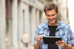 Bemannen Sie online kaufen mit einer Kreditkarte und einer Tablette stockbilder