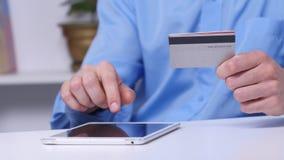 Bemannen Sie online kaufen unter Verwendung der digitalen Tabletten- und Goldkreditkarte Sehr flacher DOF! Konzentrieren Sie sich stock video