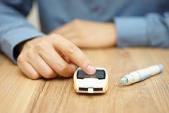 Bemannen Sie Prüfungsglukoseniveau mit einem digitalen glucometer Lizenzfreie Stockfotos