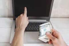 Bemannen Sie Punkt am Laptopschirm mit Dollar in der Hand Stockbild