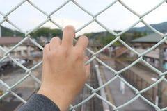 Bemannen Sie Reichweite die Stange des Käfigs mit dem defocus des Stadthintergrundes stockbild