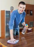 Bemannen Sie Reinigungsmöbel mit Reiniger und Lappen am Wohnzimmer stockbilder