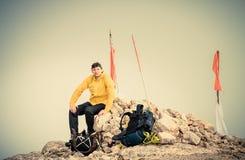 Bemannen Sie Reisenden auf Gebirgsgipfel mit Rucksack reisendem Bergsteigen Stockfotografie