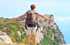Bemannen Sie Reisenden mit dem Rucksack, der Hände die im Freien steht, die zum blauen Himmel angehoben werden Stockfoto