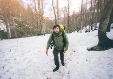 Bemannen Sie Reisenden mit dem Rucksack, der im Schneewald wandert Lizenzfreies Stockbild