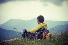 Bemannen Sie Reisenden mit dem Rucksack, der mit Bergen auf Hintergrund sich entspannt Lizenzfreies Stockbild
