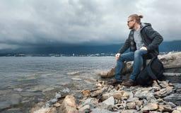 Bemannen Sie Reisenden mit ein Rucksack seets auf der Küste gegen einen Hintergrund von Wolken und ein Gebirgszugkonzept des Wand Stockbild