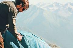 Bemannen Sie Reisenden mit kampierender Ausrüstung des Zeltes Bergen an den im Freien stockbild
