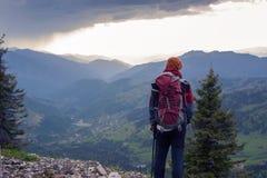 Bemannen Sie Reisendstände auf einer Klippe und Uhren der epische Sonnenuntergang Stockfotos