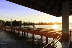 Bemannen Sie Reitfahrrad auf der Brücke mit schönem Sonnenuntergang Lizenzfreies Stockbild